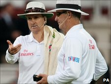 Umpires Billy Bowden (left) and Tony Hill assess the murky conditions