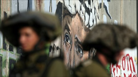 Israeli soldiers near a wall painting of Yasser Arafat near the West Bank city of Ramallah, August 2010