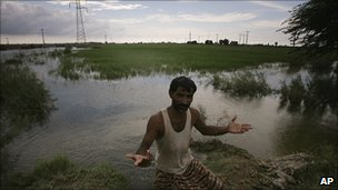 A farmer in a submerged field in Shikarpur, Pakistan, 16 August 2010