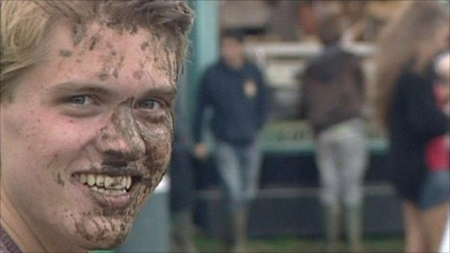 A teenager caked in mud