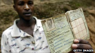A young Rwandan shows his identity card from the time of the 1994 genocide