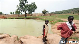 Two young boys stand next to a water hole in Dareta village, Zamfara state (June 2010)