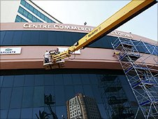 Workers hanging up brand signs on the exterior of the shopping centre