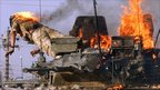British soldier jumps from a burning tank which was set ablaze after a shooting incident in the southern Iraqi city of Basra 19 September 2005.