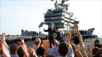"President Bush gives a ""thumbs-up"" sign as he speaks aboard the USS Abraham Lincoln"