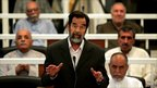 Saddam Hussein flanked by co-accused in court