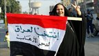 An Iraqi woman flashes the V-sign as she displays an Iraqi flag with the slogan that reads - Vote Iraq to crush terrorism - after casting her vote in central Baghdad, 15 December 2005.