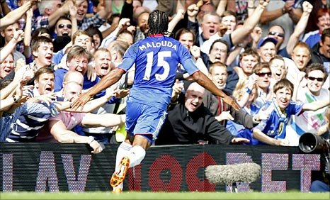 Florent Malouda wheels away to celebrate with the fans after scoring Chelsea's first