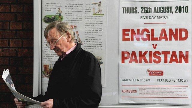 Cricket fan reading report outside Lords