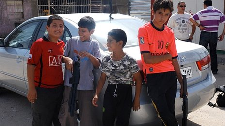 Children at a Baghdad refuge centre holding toy guns
