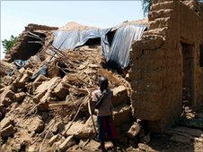 Boy stands beside his family home, destroyed by recent flooding
