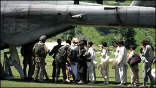 Displaced people queue up to board a US marines helicopter to be evacuated from Kalam