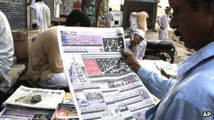 A man reads a newspaper report about the scandal in Lahore