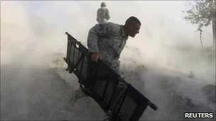 A US soldier runs to the scene of a bomb explosion in Kandahar on 30 August 2010