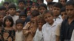 Children outside floood-damaged primary school in Nowshera, north-west Pakistan