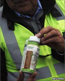A worker holds a vitamin supplement drink to be given to 33 miners trapped underground in a copper and gold mine in Copiapo, Chile