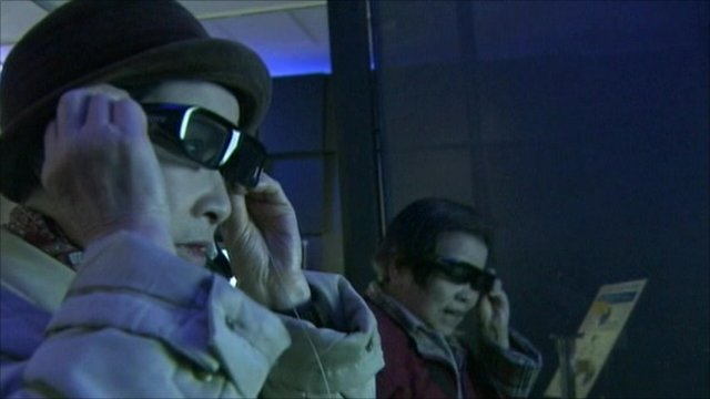 People trying on 3D glasses to watch television