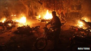 Policeman recovers his motorbike after police station is attacked in Lahore (1 September 2010)