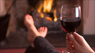Person drinking wine with feet up in front of fire