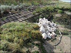 Rocks piled alongside some damaged sea wall