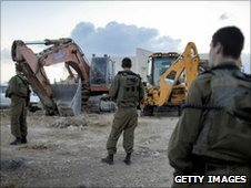 Israeli soldiers stand near construction machinery in the Jewish Settlement of Adom