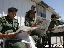 Members of the Palestinian national security forces read Arabic-language newspapers outside their post in the West Bank city of Nablus
