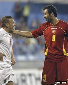 Montenegro goal scorer Mirko Vucinic (R) shares a moment with rival captain Craig Bellamy
