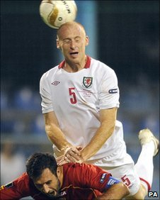 Wales defender James Collins climbs above Montenegro captain Mirko Vucinic