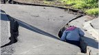 A child climbs into a seismic rupture in a road in Christchurch, New Zeland, after a powerful earthquake on 4 September, 2010