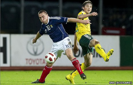 Scotland midfielder Scott Brown shields the ball from Saul Mikoliunas