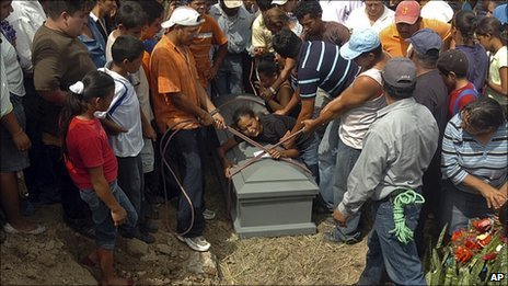 A woman cries over the coffin of her father in a cemetery in El Guante Cedros, Honduras, on 2 September, 2010