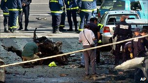 Policemen investigate the scene after an Eta car bomb exploded in Madrid, Wednesday, May 25, 2005