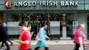 People walk past a branch of the Anglo Irish Bank in Belfast in Northern Ireland