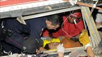 Rescuers help a survivor in a bus that was hit by a landslide in Guatemala, 4 September 2010