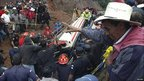 Rescuers surround a bus that was hit by a landslide in Guatemala, 5 September 2010