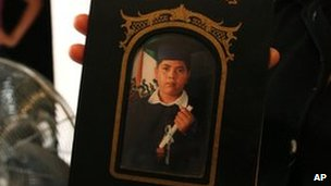 Family member holds a photograph of Alejandro Leon Castellanos, 15, shot dead with his father at a military checkpoint