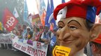 Workers carry a mask of Nicolas Sarkozy during a demonstration in Lille