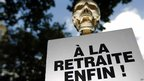 "Fake skull on top of a placard reading ""retired at last"" at a protest in Paris"