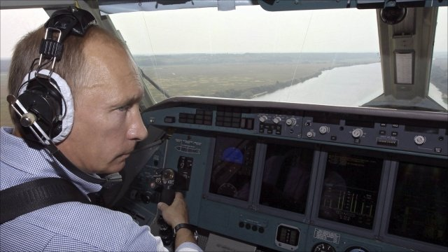 Prime Minister Vladimir Putin, wearing headphones, sits in the cockpit of a firefighting plane