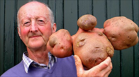 Peter Glazebrook holds up his world record potato at his home in Hallam, Nottinghamshire
