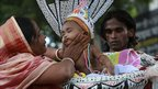 A mother tries to wake her baby son dressed as Krishna in Dhaka