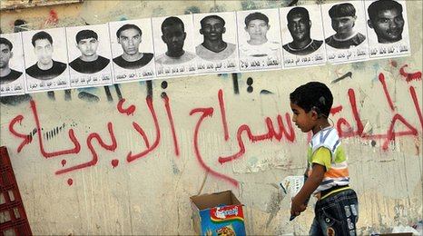 "Posters of detainees with graffiti, ""free the innocent people"" on the streets of Malkiya village, Bahrain"