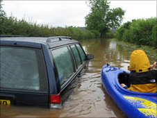 Canoeist by a submeged car