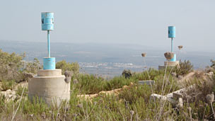 Painted oil barrels perched atop a solid concrete base along the border