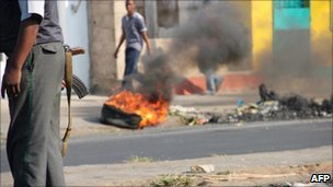 A Mozambican policeman stands near a burning tyre on a street of Maputo, 02/09