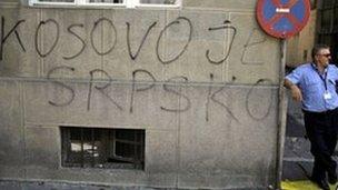 "Man standing beside graffiti saying ""Kosovo is Serbian"" in Belgrade"