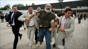 Dr Stergios Prapavezis is led away by police after throwing a shoe at the prime minister in Thessalonki (11 September 2010)