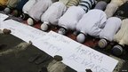 Muslims offer Friday prayers in Kolkata, near anti-US posters