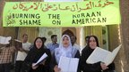 Women and men hold copies of the Koran outside Abu Hanifa mosque in Baghdad, Iraq, 10 September