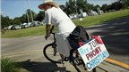 "A woman rides a bicycle with a sign reading ""Rev Jones Phony Christian"", Gainesville, Florida, 9 September, 2010"